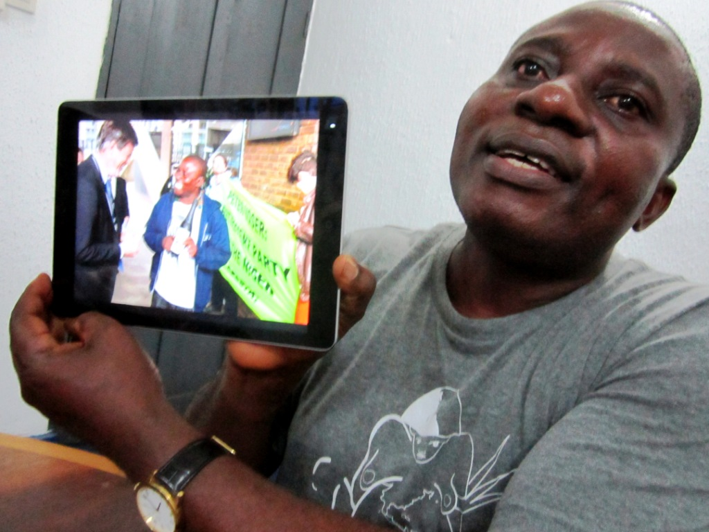 Ogoni Solidarity Forum director Celestine Akpobari showing picture with former Shell CEO Peter Voser - packed